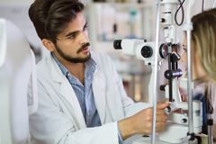 Optometrist checking patient eyesight and vision correction Stock Image
