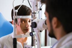Optometrist checking patient eyesight and vision correction Royalty Free Stock Photography