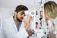 Optometrist checking patient eyesight and vision correction Stock Images