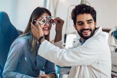 Optometrist checking patient eyesight and vision correction. Optometrist checking female patient eyesight and vision correction stock photo