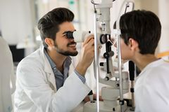 Optometrist checking patient eyesight and vision correction Royalty Free Stock Images