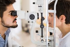 Optometrist checking patient eyesight and vision correction Stock Photography