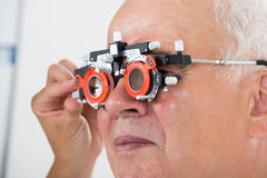 An Optometrist Checking Patient Vision With Trial Frame. Close-up Of An Optometrist Checking Senior Male Patient Vision With Trial Frame At Eye Clinic Stock Photo