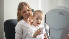 Optometrist checks child`s eyesight - mother and child in ophthalmologist room. Horizontal stock photography