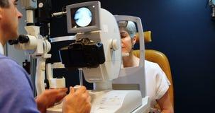 Optometrist die geduldige ogen met autorefractors 4k onderzoeken stock videobeelden