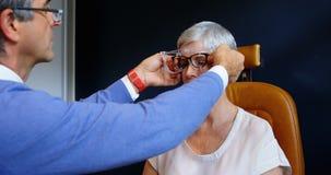 Optometrist die geduldige ogen met het materiaal 4k onderzoeken van de oogtest stock footage