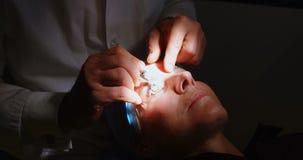 Optometrist die geduldige ogen met het materiaal van de oogtest in kliniek 4k onderzoeken stock video