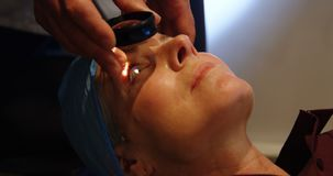 Optometrist die geduldige ogen met het materiaal van de oogtest in kliniek 4k onderzoeken stock footage