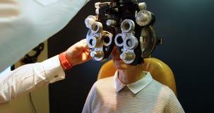 Optometrist die geduldige ogen met phoropter 4k onderzoeken stock footage