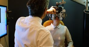 Optometrist die geduldige ogen met phoropter 4k onderzoeken stock video