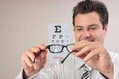 Optometrist die oogglazen onderzoekt Royalty-vrije Stock Afbeelding