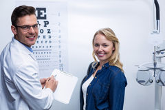 Optometrist discussing eye test report with female patient Royalty Free Stock Photo