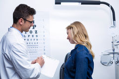 Optometrist discussing eye test report with female patient Stock Photo