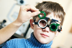Optometrist doctor examines eyesight of child boy with phoropter Stock Photos
