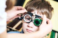 Optometrist doctor examines eyesight of child boy with phoropter Stock Photo