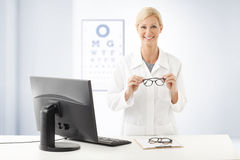 Optometrist doctor portrait. Portrait of smiling optometrist doctor standing ad desk in front of computer and holding hands eyewear. In the background with an Royalty Free Stock Photography