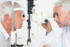 Optometrist doing sight testing for senior patient Royalty Free Stock Photo
