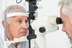 Optometrist doing sight testing for senior patient Stock Images