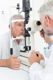 Optometrist doing sight testing for senior patient. Close-up of an optometrist doing sight testing for senior patient Stock Image