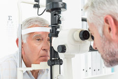 Optometrist doing sight testing for senior patient royalty free stock images