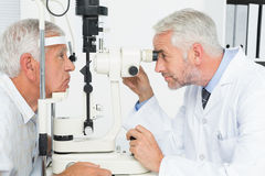 Optometrist doing sight testing for senior patient Stock Image