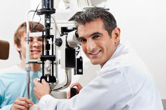 Optometrist Doing Visual Field Test On His Patient. Portrait of a smiling optometrist while performing visual field test on his patient royalty free stock images