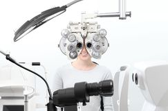 Optometrist exam, eyesight woman patient with phoropter in opti. Cian office stock image