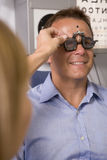 Optometrist in exam room with man in chair Royalty Free Stock Photo