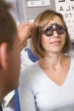 Optometrist in examenruimte met vrouw Royalty-vrije Stock Foto's