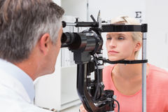 Optometrist examining blonde woman Royalty Free Stock Photos