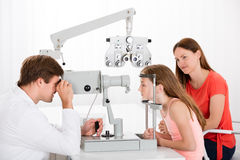 Optometrist Examining Eyesight Of Girl. Male Optometrist Examining Eyesight Of Girl While Mother Sitting Beside Her royalty free stock images