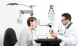Optometrist examining eyesight patient in optician office on wh stock images