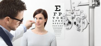 Optometrist examining eyesight, woman patient pointing at the ch stock image