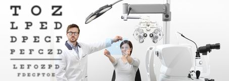 Optometrist examining eyesight woman patient pointing chart at t. Optometrist examining eyesight women patient pointing chart at the hole on plexiglass in Royalty Free Stock Image