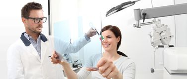 Optometrist examining eyesight, woman patient pointing at the ho. Optometrist examining eyesight, women patient pointing at the hole on plexiglass, ocular Royalty Free Stock Photos