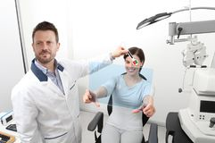 Optometrist examining eyesight, woman patient pointing at the ho. Optometrist examining eyesight, women patient pointing at the hole on plexiglass, ocular Royalty Free Stock Photography