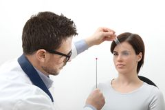 Optometrist examining eyesight, woman patient pointing at the sp stock photography