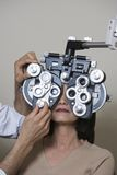 Optometrist Examining Female Patient. An optometrist adjusting panels of phoropter while examining female patient over grey background royalty free stock photo