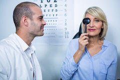 Optometrist examining female patient with medical equipment Royalty Free Stock Image