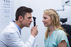 Optometrist examining female patient through ophthalmoscope Royalty Free Stock Images
