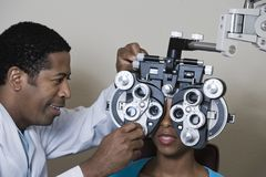 Optometrist Examining Patient. An African American male optometrist adjusting panels of phoropter while examining patient over grey background stock photos