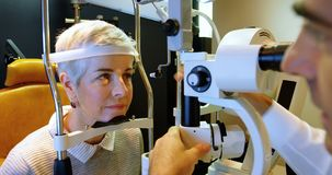 Optometrist examining patient eyes with slit lamp 4k