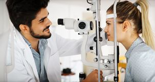 Optometrist examining patient in modern ophthalmology clinic. Optometrist examining patient in ophthalmology clinic with professional equipment Stock Photography