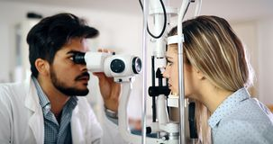 Optometrist examining patient in modern ophthalmology clinic. Optometrist examining patient in ophthalmology clinic with professional equipment Stock Images