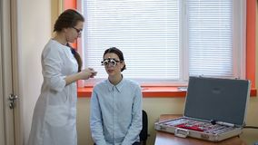 Optometrist examining patient with trial frame stock footage