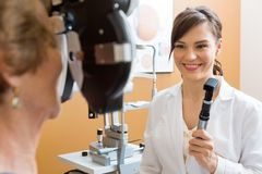 Optometrist Examining Senior Woman's Eyes Stock Photography