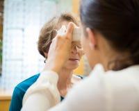 Optometrist Examining Senior Woman's Vision Stock Photo