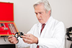 Optometrist Examining Trial Frame For Eye Test Royalty Free Stock Photos