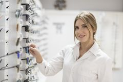 Optometrist in eyeglasses store selecting lenses. And looking at camera Stock Image