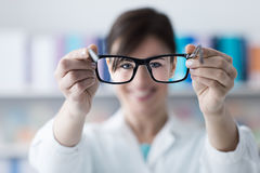 Optometrist giving glasses to the patient stock images
